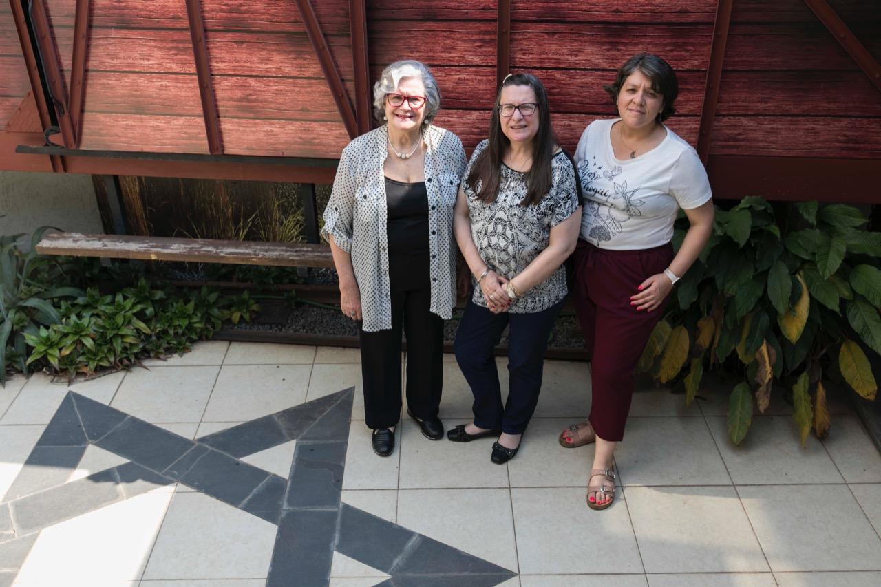 Ruth Kohan, Mónica Strupp-Schvartzman y Romina Burgos Mancini junto a la imagen que evoca los trenes del Holocausto © Laura Mandelik